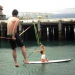 waterline-slackline-blond-girl-on-stand-up-paddle-board